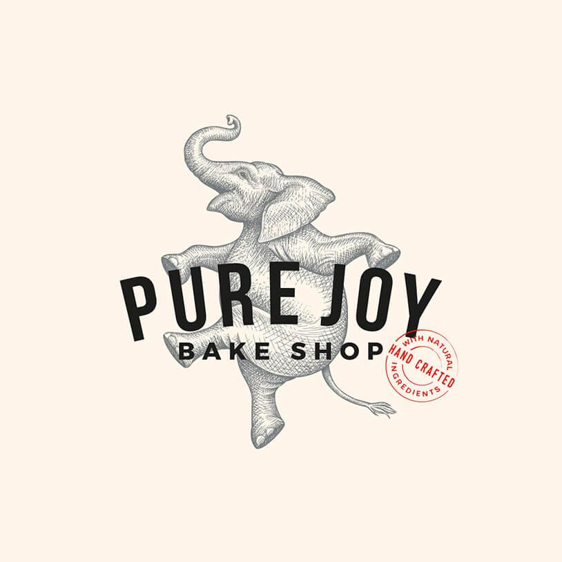 Логотип с довольным слоном в прыжке надписью Pure Joy Bake Shop