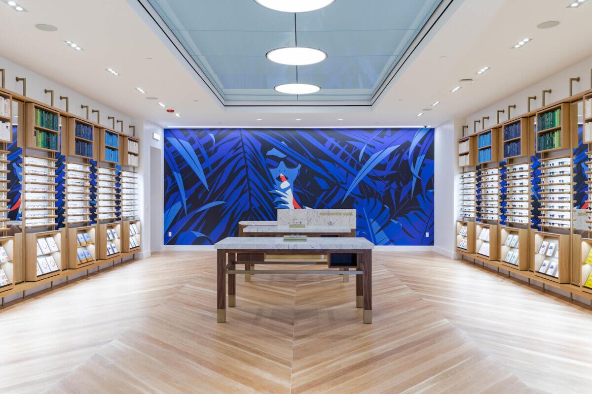 синяя иллюстрация в магазине Warby Parker с женщиной в очках, которая выглядывает из кустов