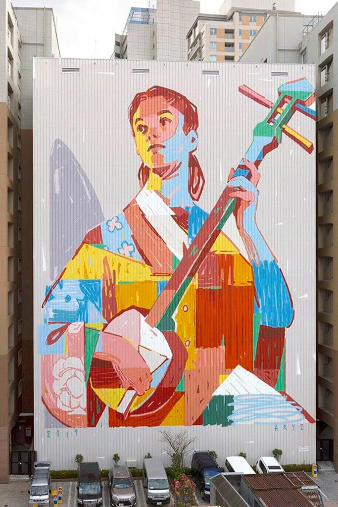 Мурал женщины с музыкальным инструментом на стене высотного здания